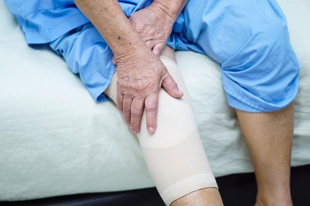 Asiatique senior ou vieille dame âgée patiente avec joint de douleur de soutien du genou. Photo Premium