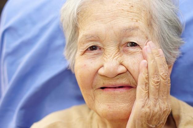 Asiatique Senior Ou Vieille Dame Vieille Femme Souriant Avec La Main Touchant Sur Son Visage. Concept Médical, Heureux Et Portrait. Photo Premium