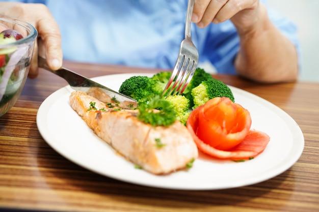Asiatique senior vieille femme patiente manger petit-déjeuner des aliments sains à l'hôpital. Photo Premium