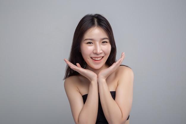 La asiatique surprise a posé sa main sur son menton. Photo gratuit