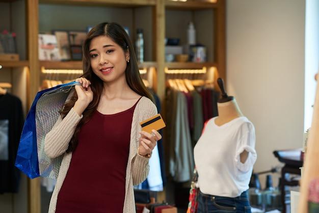 Asiatique tenant une carte en plastique et sac à provisions debout dans le magasin de vêtements Photo gratuit
