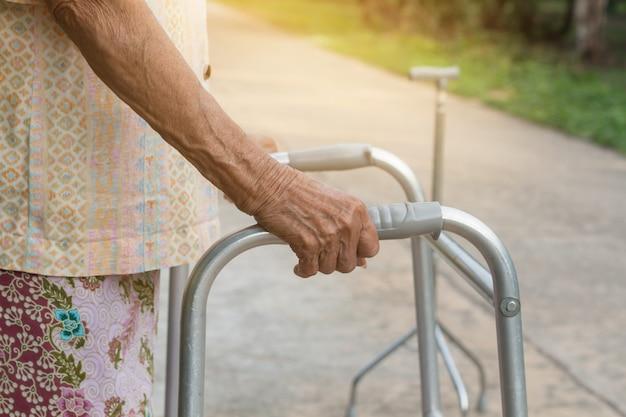 Asiatique vieille femme debout avec ses mains sur un bâton de marche Photo Premium
