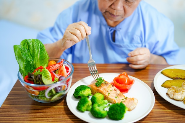 Asiatique vieille femme patiente manger des aliments sains. Photo Premium