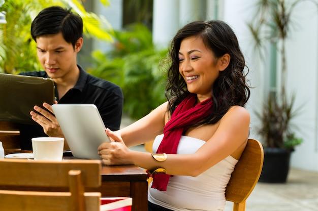 Asiatiques au café avec ordinateur Photo Premium