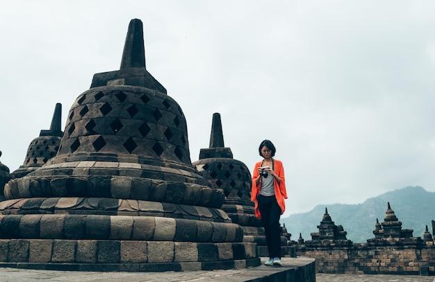 Asiatiques femmes voyageurs individuels prennent photo bâtiments anciens au temple de borobudur, java, indonésie Photo Premium