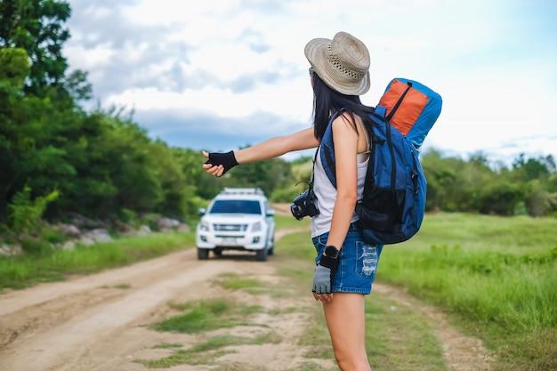 Asie femme voyageur faisant de l'auto-stop pour aller à destination dans son voyage. Photo Premium