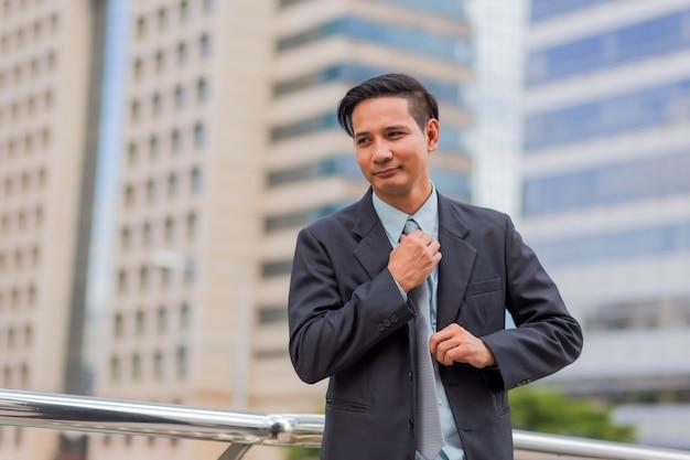 Asie jeune homme d'affaires en face de l'immeuble moderne au centre-ville Photo Premium