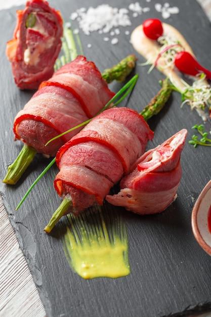 Asperges roulées au bacon grillé servies avec une sauce sur une assiette noire Photo Premium