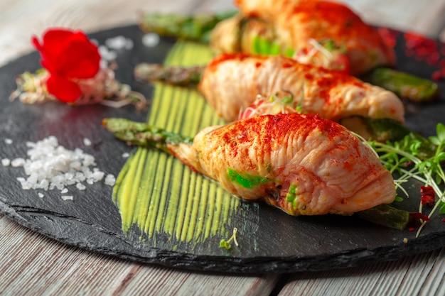 Asperges roulées avec des tranches de viande de poulet servies sur une assiette noire Photo Premium