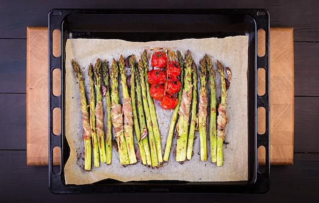 Asperges vertes grillées, enveloppées de bacon sur une table en bois. vue de dessus Photo Premium