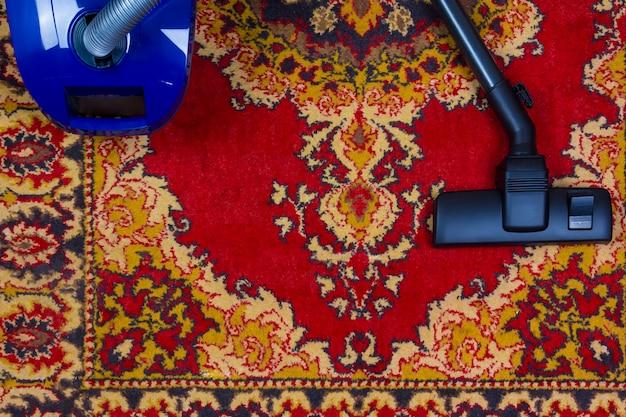 Aspirateur électrique sur le fond d'un vieux tapis, vue de dessus d'un appartement poser Photo Premium