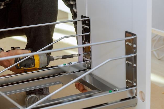 Assemblage du meuble en vissant le meuble dans la cuisine à l'aide d'un tiroir à tournevis sans fil Photo Premium