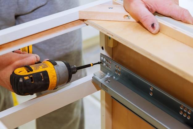 Assemblage des tiroirs à charnière sur la porte du meuble de cuisine Photo Premium