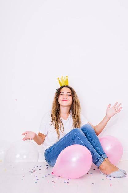 Asseyez-vous fille entourée de ballons Photo gratuit