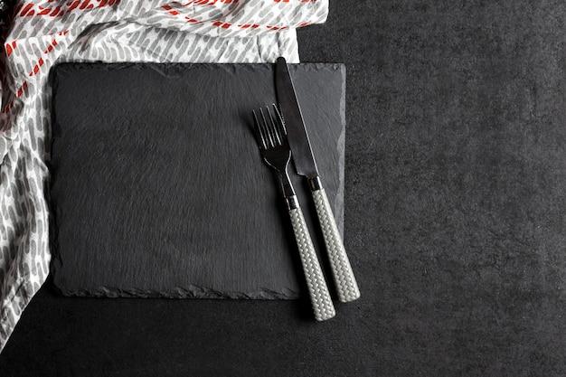 Assiette En Ardoise Noire Avec Fourchette Et Couteau Et Nappe Photo Premium