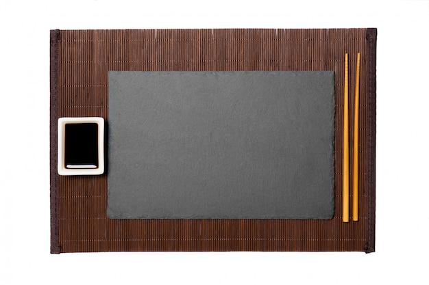 Assiette En Ardoise Noire Rectangulaire Vide Avec Des Baguettes Pour Sushi Et Sauce Soja Sur Fond Mat En Bambou Foncé. Photo Premium