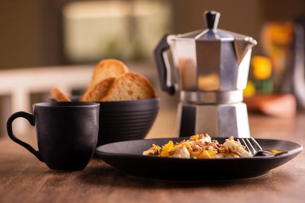 Assiette De Banane En Tranches Avec Granola, Fruits Confits Et Miel, Pain Grillé Et Une Tasse De Café Photo Premium