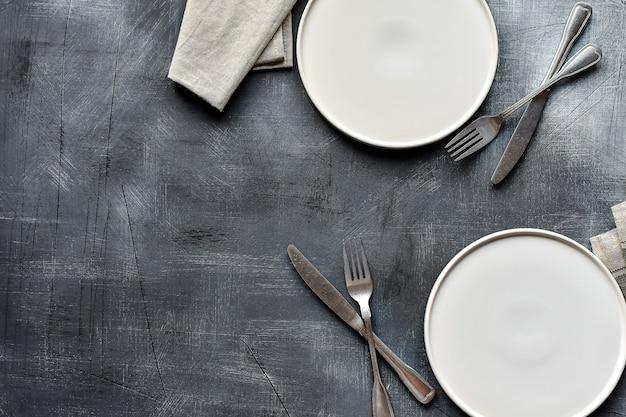 Assiette Blanche, Couverts Et Serviette De Table Sur Une Table En Pierre Sombre. Réglage De La Table Photo Premium