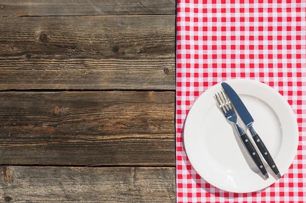Assiette Blanche Sur Nappe à Carreaux Et Planche De Bois Texturée Photo gratuit