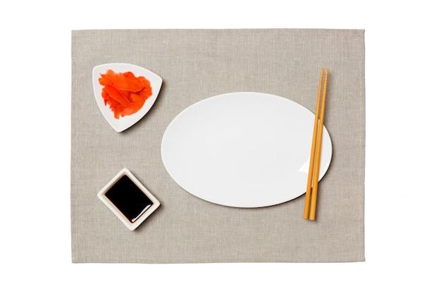 Assiette Blanche Ovale Vide Avec Des Baguettes Pour Sushi, Gingembre Et Sauce Soja Sur Fond De Serviette Gris Photo Premium