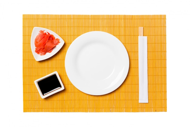 Assiette Blanche Ronde Vide Avec Des Baguettes Pour Sushi Et Sauce Soja, Gingembre Sur Fond De Tapis De Bambou Jaune Photo Premium