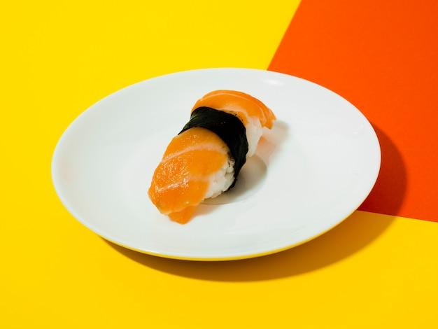 Assiette blanche avec sushi sur fond jaune et orange Photo gratuit