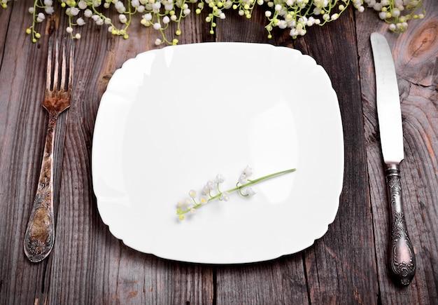 Assiette blanche vide avec des couverts en fer Photo Premium