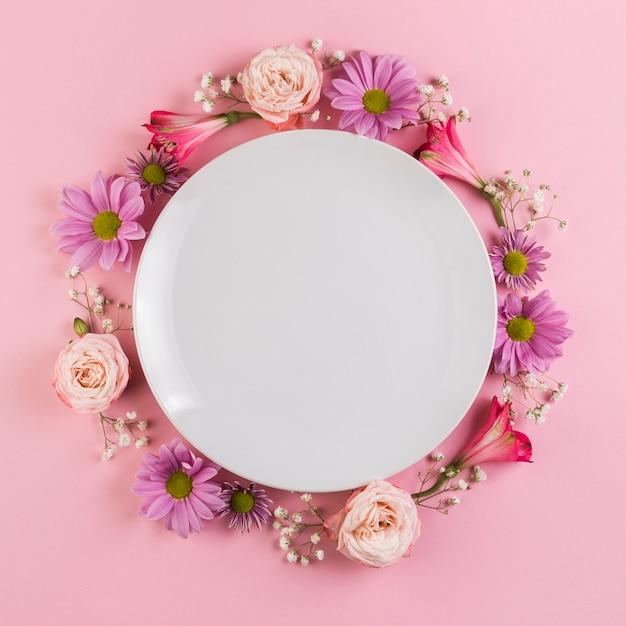 Une assiette blanche vide décorée de fleurs colorées sur fond rose Photo gratuit