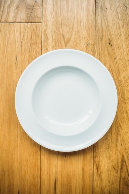 Assiette blanche vide sur fond en bois Photo gratuit