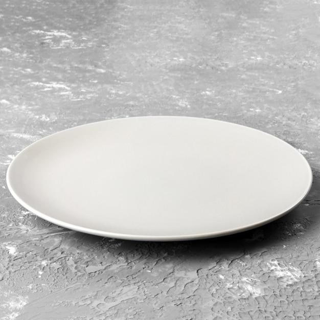 Assiette blanche vide sur une surface rugueuse Photo Premium