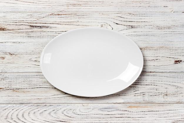Assiette blanche vide sur une table en bois. vue de dessus Photo Premium