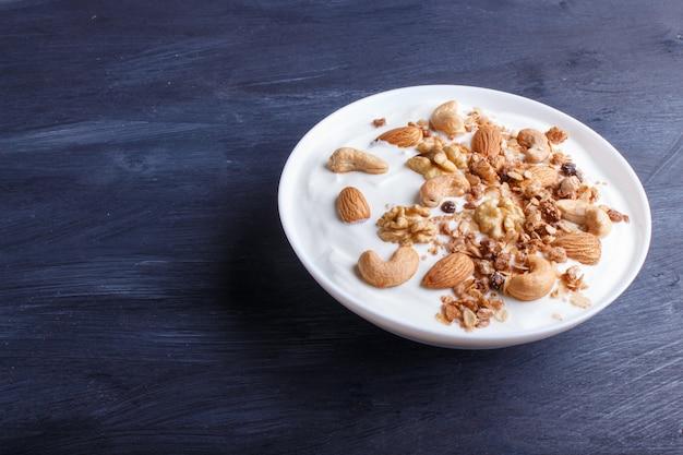 Assiette blanche avec yaourt grec, granola, amande, noix de cajou, noix de grenoble sur bois noir. Photo Premium