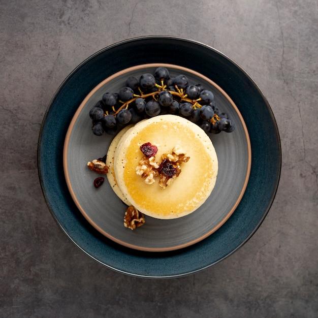 Assiette bleu foncé avec des crêpes et des raisins sur un fond gris Photo gratuit