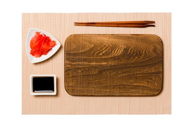 Assiette En Bois Brun Rectangulaire Vide Avec Des Baguettes Pour Sushi, Gingembre Et Sauce Soja Sur Fond De Tapis De Sushi Brun. Vue De Dessus Avec Espace De Copie Pour Votre Conception Photo Premium