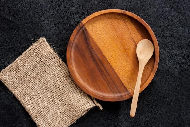 Assiette en bois et cuillère en bois mise sur un sac de cuisine fait maison Photo Premium