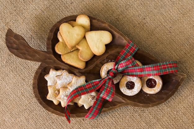 Assiette en bois avec différents biscuits sur la table Photo gratuit