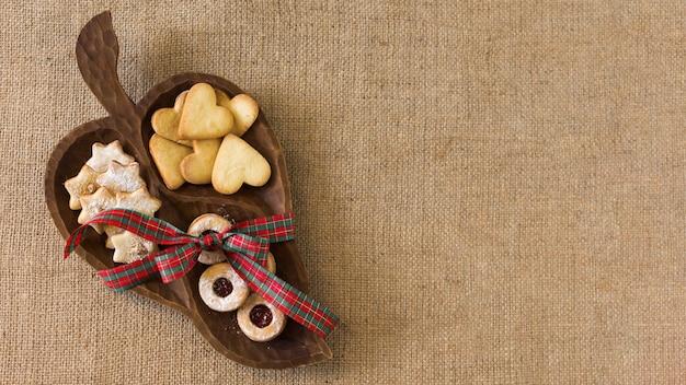 Assiette en bois avec différents biscuits Photo gratuit