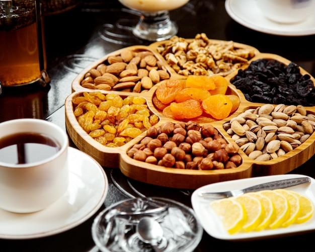 Assiette En Bois Avec Fruits Secs Et Noix Photo gratuit