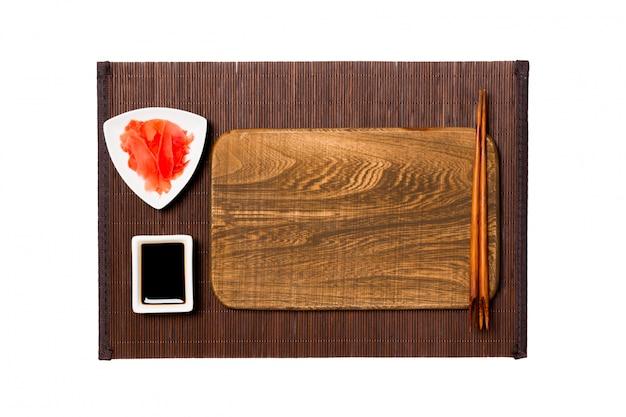Assiette en bois marron rectangulaire vide avec baguettes pour sushi, gingembre et sauce soja sur tapis de bambou foncé. vue de dessus avec fond Photo Premium