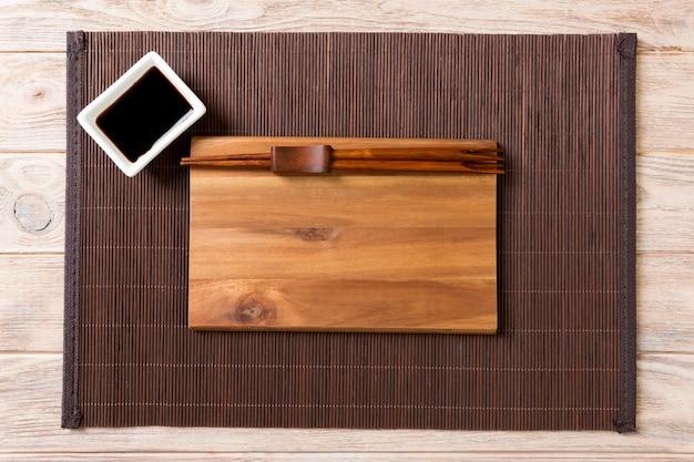 Assiette en bois vide avec des baguettes pour sushi et sauce soja sur bois. Photo Premium
