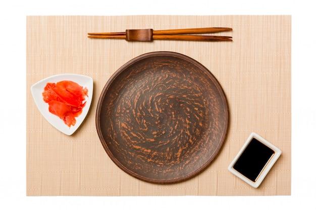 Assiette Brune Ronde Vide Avec Des Baguettes Pour Sushi Et Sauce Soja, Gingembre Sur Tapis De Sushi Brun. Vue De Dessus Avec Espace De Copie Pour Votre Conception Photo Premium