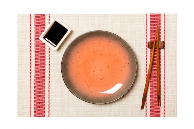 Assiette Brune Ronde Vide Avec Des Baguettes Pour Sushi Et Sauce Soja Photo Premium