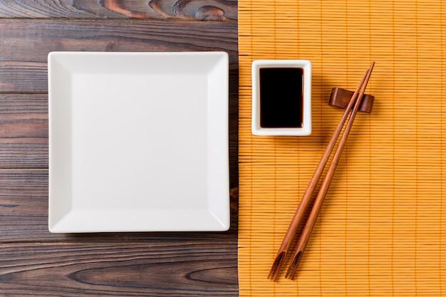 Assiette Carrée Blanche Vide Avec Des Baguettes Pour Sushi Et Sauce Soja Photo Premium