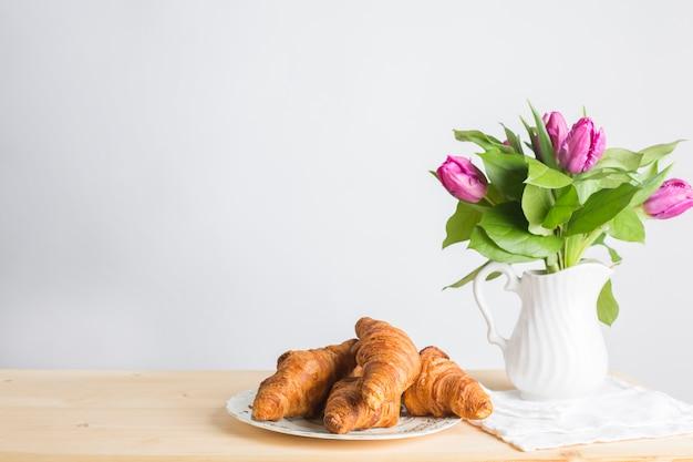 Assiette De Croissants Au Four Près Du Vase Sur Un Bureau En Bois Isolé Sur Fond Blanc Photo gratuit