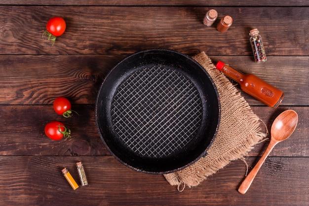Assiette, cuillère, épices et autres accessoires de cuisine sur un fond en bois foncé Photo Premium
