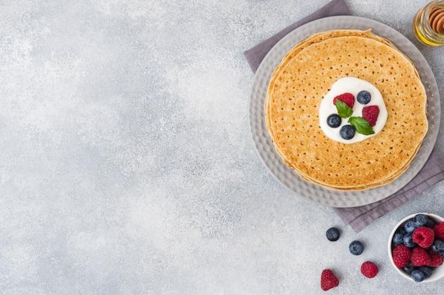 Assiette de délicieuses crêpes minces aux baies sur une table grise Photo Premium