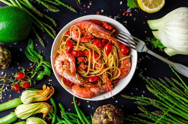 Une assiette de délicieuses pâtes italiennes aux crevettes tigrées ou aux crevettes et légumes frais sur fond noir Photo Premium