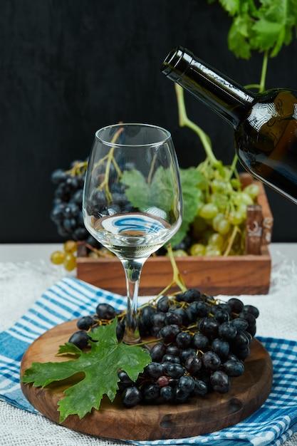 Assiette De Divers Raisins Et Un Verre De Vin Sur Table Blanche Avec Bouteille De Vin Photo gratuit