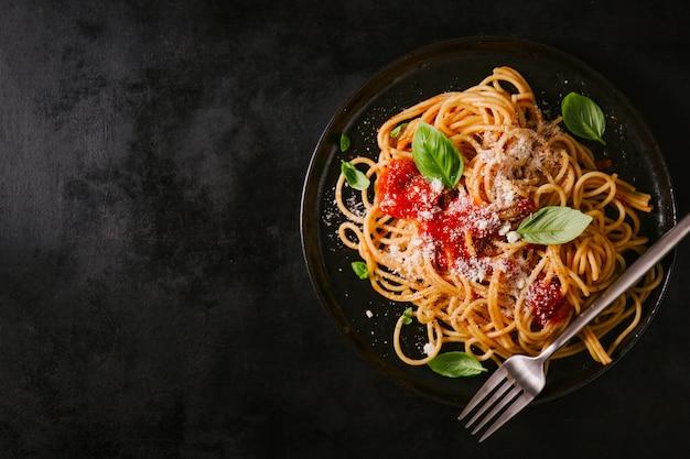 Assiette foncée avec spaghetti italien sur fond noir Photo Premium
