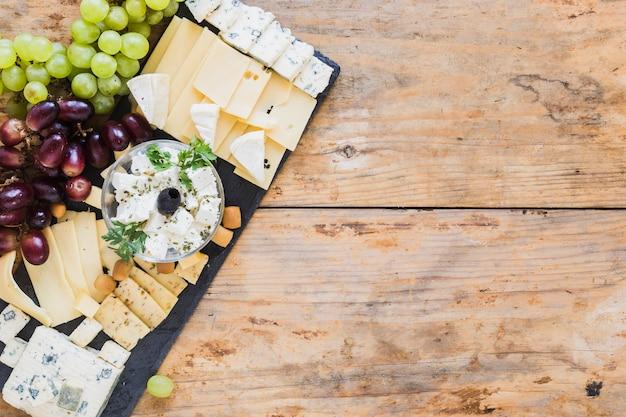 Assiette de fromages aux raisins sur ardoise noire au-dessus de la table Photo gratuit